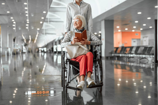 Young female worker of airport holding wheelchair with elderly lady in hall