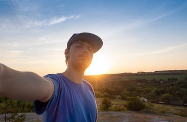 Teenager hipster traveler doing selfie overlooking on sunset. Wanderlust, Adventure, Vacation, concept.
