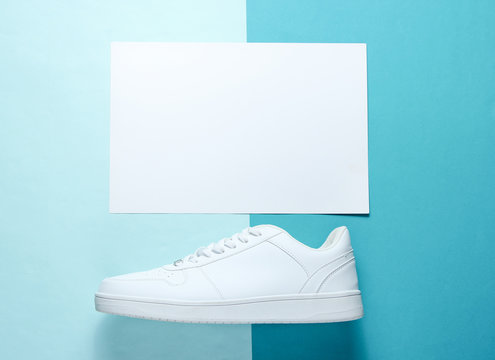 White sneaker on a blue background with a white sheet of paper for copy space, top view