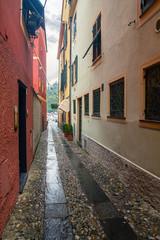 Een smal geplaveid steegje (&quot caruggio&quot  in het Genuese) dat leidt naar het beroemde plein Piazza Martiri dell& 39 Olivetta, simpelweg &quot Piazzetta&quot  genoemd, in het centrum van Portofino, Genua, Ligurië, Italië