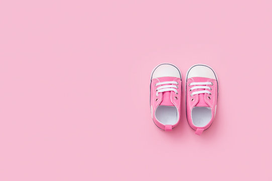 Cute pink baby girl sneakers close up on pink background