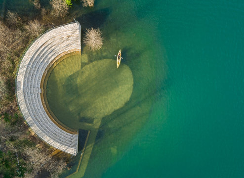 Aerial view of person kayaking next to old amphitheater at beautiful lake Plastira in Greece