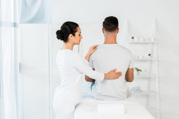 back view of man sitting on massage table near brunette healer