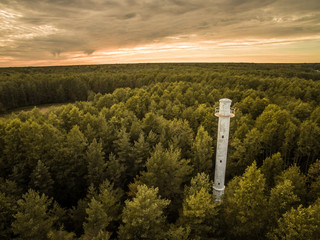 Aerial view of a lighthouse in the middle of forest with a stormy sky in Estonia.