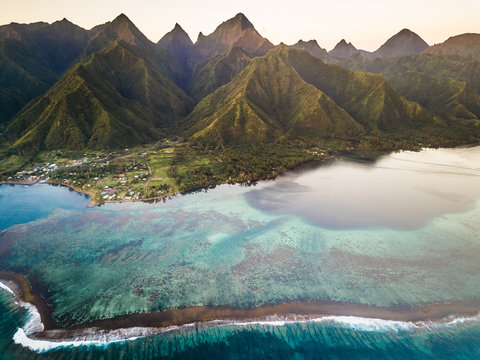 Aerial view of coral reef with The Mighty Mount Aorai in the background in Tahiti, French Polynesia.