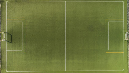 Aerial view of a green synthetic football pitch with white and yellow lines.