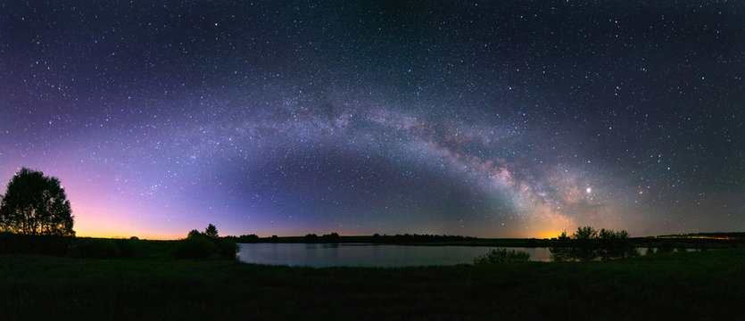 Night panorama of the arch of the Milky Way, above the lake in the northern hemisphere