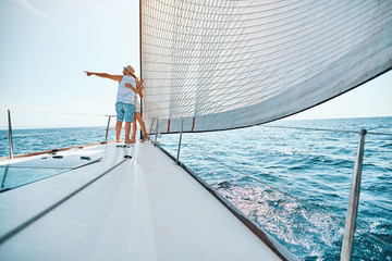 Young couple in love sailing sailboat yacht..