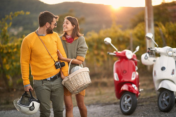 Man and woman on romantic road trip on scooter at sunset..