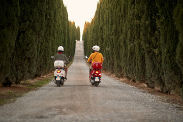 Man and woman on romantic road trip on scooter at sunset. Back view..