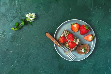 Chocolate rollcake with fresh strawberries in ceramic plate