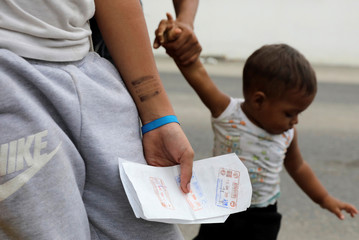 Venezuelan girl Uslady holds papers after she and her family finished immigration procedures ahead of a June 15 deadline of new immigration laws, in Tumbes