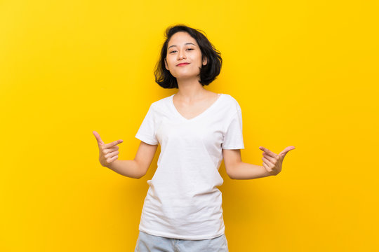 Asian young woman over isolated yellow wall proud and self-satisfied
