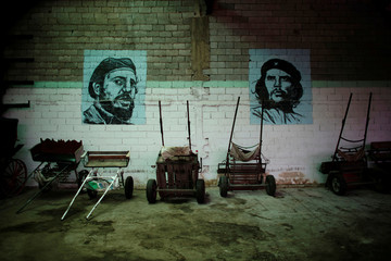 "Images of late Cuban President Fidel Castro and late revolutionary hero Ernesto ""Che"" Guevara are displayed on the wall of a stable in Havana"