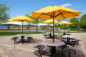 Resting area in park with seats, tables and parasol