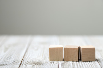 Three wooden toy cubes arranged in row on white grey wooden background