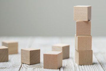 Four wooden toy cubes arranged in vertical on white grey wooden background