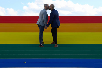 Daniel Diaz and Juan Jose Acosta, both from Brooklyn, kiss during an engagement photo shoot on a giant LGBTQ Pride Flag installed on the steps of Franklin D. Roosevelt Four Freedoms State Park to celebrate WorldPride in New York City