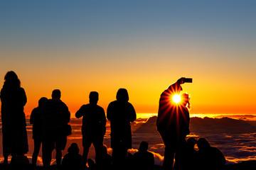 Silhouette of crowd enjoying the sunset atop Mount Haleakala on Maui, Hawaii