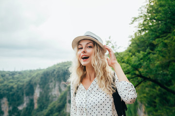 b8e17e766b6f1 cheerful lady with blond flowing hair in a big white polka-dot shirt  holding a