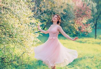 db62f85db7d8e happy girl in short flying gentle pink dress laughs joyfully, doll princess  whirls in bright