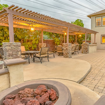 Square frame Patio with dining area and built in circular benches wrapped around a fire pit