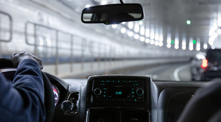Driving in Lincoln tunnel, New York. Close up view on cab driver hand and dashboard