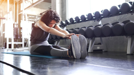 Woman in an athletic look with aerobic exercise stretching loosening the muscles in various positions while on the exercise mat.