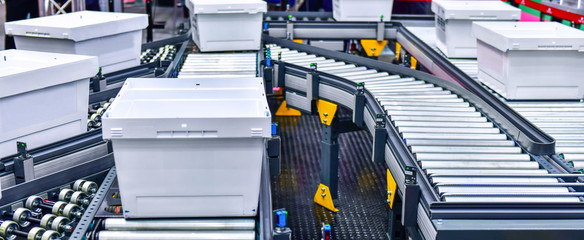 White plastic box on conveyor belt.parcels transportation system concept