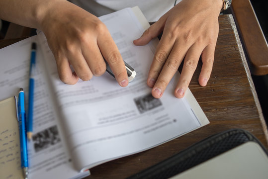 Close up of student hand using eraser on English workbook
