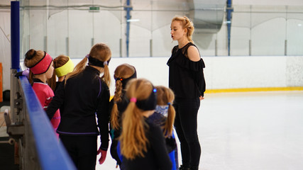Female coach in figure skating talk to girls at indoor rink