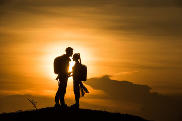 Silhouette couple on the mound in the sunset sky