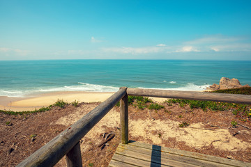 The wooden platform on a rocky seashore on a sunny day. Victory Walls Beach, Portugal, Europe