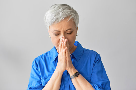 Horizontal shot of beautiful gray haired stylish retired woman in blue shirt closing eyes and holding hands at her face worrying about het troubled son. Mature lady covering mouth while sneezing