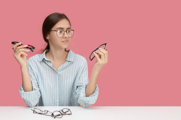 Vision, optics, eyesight, myopia, people and eyewear concept. Picture of stylish beautiful short sighted young female choosing distance glasses, holding two pairs of spectacles, having indecisive look