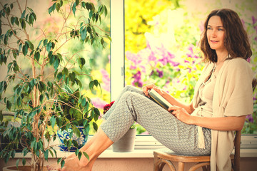 beautiful woman with a book near the window