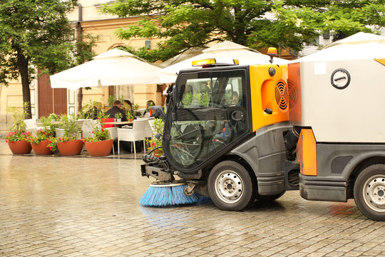 A street sweeper sweeps up a stone pavement with a strong brush in rainy weather. Maintaining clean tourist city. Preventing environmental disaster. Budget item of the city. Automation of the janitor