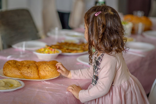 Little jewish curly girl placing challah bread on a table for Shabbat meal.