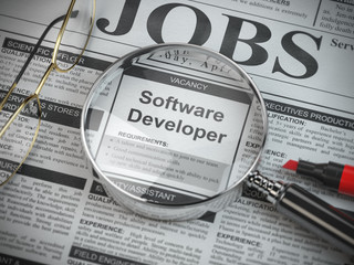 Software developer vacancy in the ad of job search newspaper with loupe.