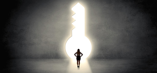 Woman standing alone in front of a big keyhole