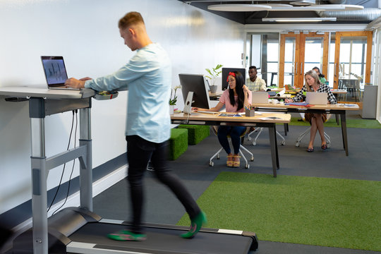 Businessman working on laptop while exercising on treadmill in a modern office