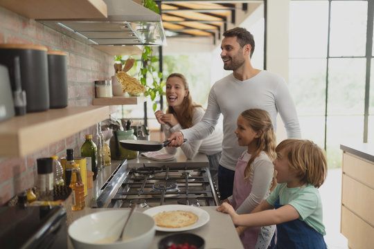Family preparing food in kitchen at home