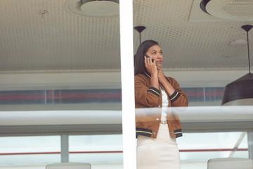 Businesswoman talking on mobile phone near window in a modern office