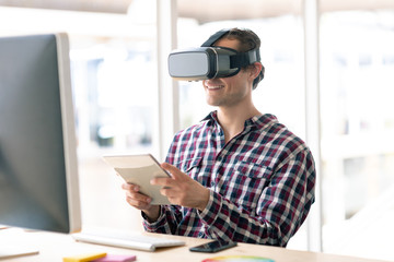 Male graphic designer using virtual reality headset while working on digital tablet at desk