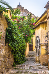 Fototapete - Scenic narrow street with old houses in Plaka district, Athens, Greece. Plaka is one of the main tourist attractions of Athens. Vintage traditional alley overlooking the famous Acropolis of Athens.