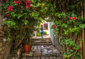 Beautiful narrow street with flowers in Plaka district, Athens, Greece. Scenic alley like overgrown tunnel in the Athens center. Young woman in the distance. Concept of travel and vacation in Athens.