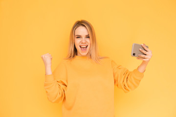Joyful blond girl in a bright casual clothing holds a smartphone in her hands, looks in camera and shouts.Smiling teenage girl with a phone in her arms rejoices on a yellow background
