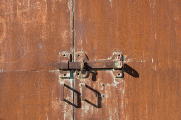 Background of old iron rusty gate. Metal gate with red rust. The texture of a rusty gate with a hinged and padlock lock. Gates with door handles. Wall mural