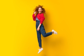 Redhead woman with overalls jumping over isolated yellow wall Wall mural