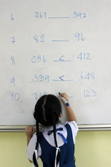 Primary school girl solves greater than or less than math equations on a classroom whiteboard